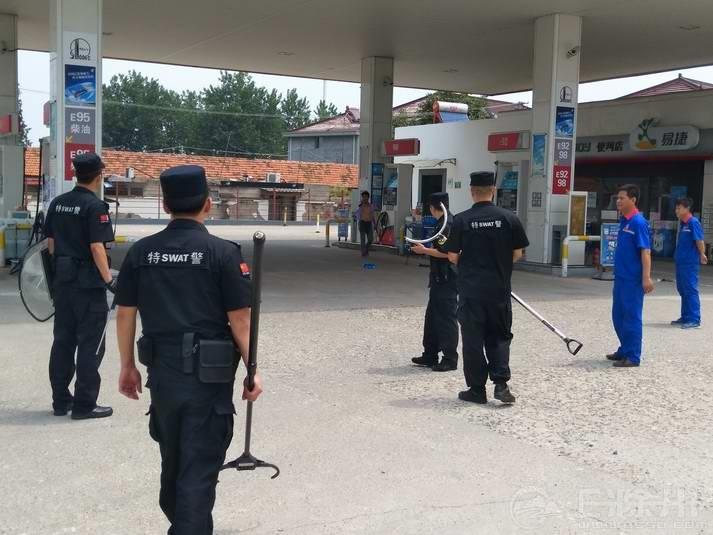 4、民警和加油站员工在事发现场.JPG